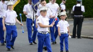 Young boys carrying batons leading the parade