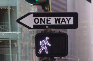 A one-way sign pointing left whilst a green man above it faces the other way.