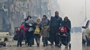 Syrian residents arrive in Aleppo's Fardos neighbourhood after fleeing the violence of Bustan al-Qasr, 13 December 2016