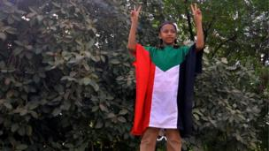 طفل تزينت بعلم السودان وتلوح بعلامة النصر