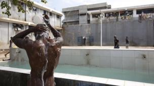 A prisoner bathes during recreation time inside the National Penitentiary in downtown Port-au-Prince