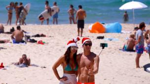 Tourists take a selfie as they wear Christmas hats and celebrate Christmas Day at Sydney's Bondi Beach in Australia, 25 December, 2016.