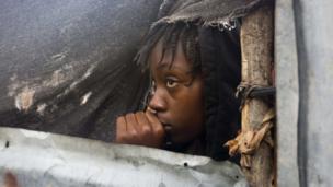 Msichana mdogo aangalia wakati maafisa walipofika kuondoa familia yake Tabarre, Haiti.