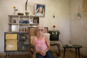A woman sits in her house