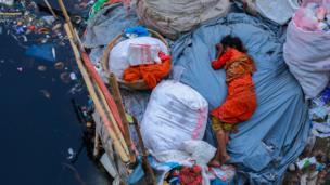 Mujer durmiendo a orillas de un río contaminado