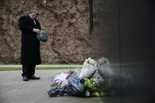 A man pauses in front of floral tributes
