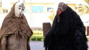 Des personnes vêtues de masques typiques accueillent les invités lors de la cérémonie d'ouverture et d'inauguration du nouveau musée des civilisations noires, à Dakar,