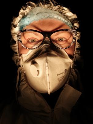 Enfermeira usando máscara com fundo escuro atrás