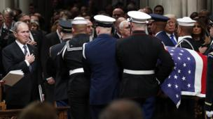George W Bush places his hand on his chest as his father's casket is carried from the cathedral