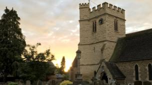 The sun rising over St Andrews Church in Old Headington