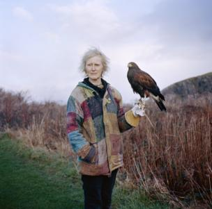A woman in a colourful jacket stands in the countryside and holds a hawk