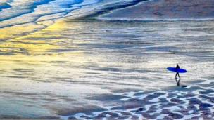 Caswell Bay, Gower, at sunset with a surfer walking on the beach holding a blue surfboard