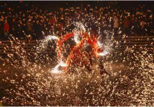 """2月16日晚,在山东台儿庄古城,民间艺人为游客表演""""火龙钢花""""。"""