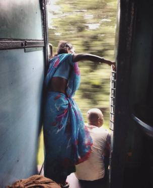 A woman peers out of a moving train, looking for her stop.