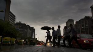 Indian commuters walk home in the rain in New Delhi, India, Monday, May 23, 2016.