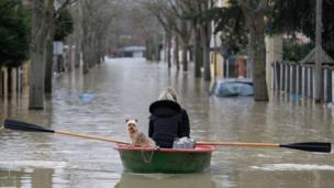 A residents and her dog use a rowboat to get down a flooded street in Villeneuve-Saint-Georges on the southern outskirts of Paris on 24 January 2018