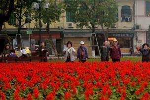 Grupo de mujeres haciendo ejercicio frente a flores.