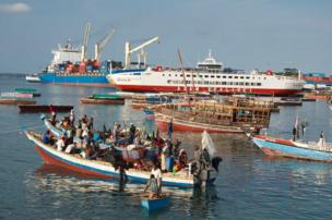 An large shipping container is contrasted with smaller boats carrying goods to supply the local market