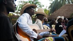 Churchill Olum playing a guitar in Kampala