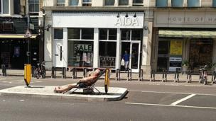 Man sunbathing on a central reservation