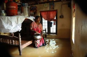 એક મહિલાની તસવીર જેમનાં ઘરમાં પાણી ઘૂસી ગયું છે.