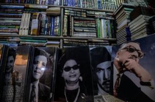صور عمالقة الفن و الساسية المصريين تصطف في محل بسور الأزبكية في القاهرة