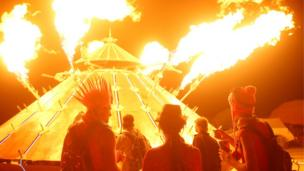 Participants watch the flames of the mutant vehicle as approximately 70,000 people from all over the world gather for the 30th annual Burning Man arts and music festival in the Black Rock Desert of Nevada
