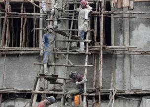 عمال بناء فوق سقالة خشبية