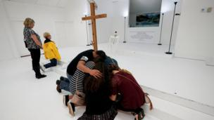 People pray in the First Baptist Church of Sutherland Springs, Texas, as the church was opened to the public as a memorial to those killed on November 12, 2017