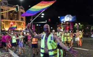 A man holding a rainbow flag gestures to the camera