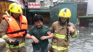 Fire rescue workers rescue a woman in floodwaters in the village of Lei Yu Mun during Super Typhoon Mangkhut in Hong Kong on 16 September 2018.