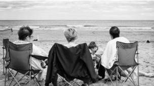 समुद्री किनारे पर मजे करती तीन औरतें