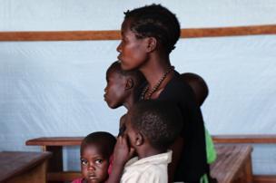 Une mère assise dans un centre de santé provisoire avec ses enfants malades en attente des soins.