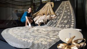 """Curator Caroline de Guitaut adjusts Queen Elizabeth II""""s wedding dress designed by Sir Norman Hartnell in 1947"""