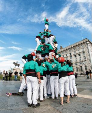 A tower made out of people standing on each other's shoulders