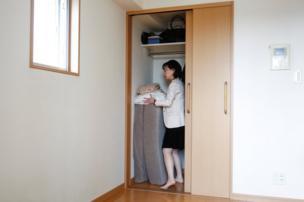 Minimalist Saeko Kushibiki stores away her futon mattress in her apartment in Fujisawa