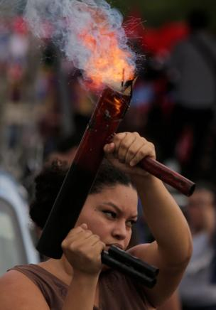 A woman fires a home-made mortar vertically into the air during a pro-government rally
