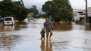 أب وطفله يسيران في شارع تغمره مياه الفيضانات.