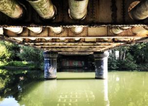 A bridge covered in graffiti sit over a green canal