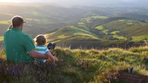 Father and son, Dafydd and Cynan Hughes, take in the views above Esgair llyn near Machynlleth