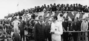 14th July 1967: During a pit stop before a practice lap at Silverstone, racing driver Jim Clark (1936 - 1968) on right in white. talks with racing boss Colin Chapman (1928 - 1981) founder of Lotus cars. Figure in racing gear on the left talking to a mechanic is racing driver Graham Hill (1929 - 1975)