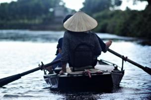 Vietnamese men and women row tourists