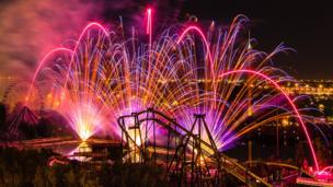 A firework display amongst rollercoasters