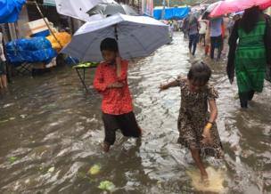 Two children with umbrellas on a flooded street