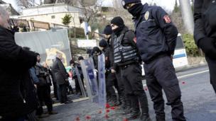Люди приносят цветы на место трагедии, которое оцепила полиция.