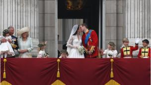 Prince William and Kate Middleton kiss on the balcony of Buckingham Palace on their wedding day, surrounded by their wedding party.