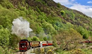 A photograph an old steam train on a railway. It's purple in colour and there's is a plume of white smoke coming from the funnel. In the background there is a rugged Welsh green hillside and a blue sky, with a couple of fluffy white clouds
