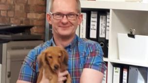 توماس يحمل كلبه رالفي في مكان العمل