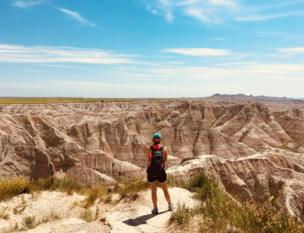 A woman stands above looking over canyons