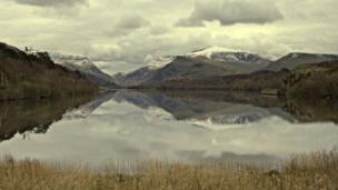 Snow-capped mountains behind Llyn Padarn in Snowdonia